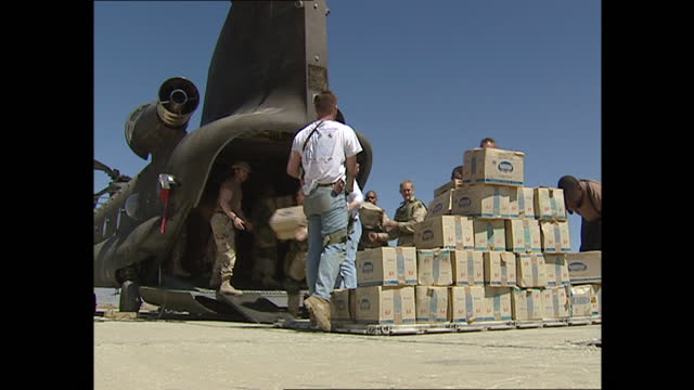exterior shots of aid packages baing loaded into helicopters by soldiers following a earthquake in the hindu kush region on 28th march 2002 in bagram... - bagram stock videos & royalty-free footage