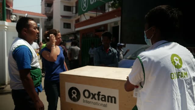 Exterior shots of aid workers moving boxes of aid donated by Oxfam into trucks and stacking up buckets on May 3 2015 in Kathmandu Nepal