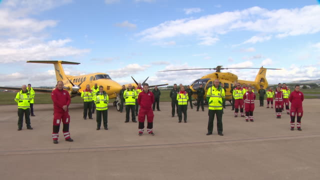 exterior shots of air ambulance staff taking part in minute silence for nhs staff held across the uk to commemorate the key workers who have died... - tribute event stock videos & royalty-free footage