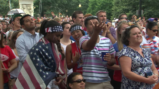 stockvideo's en b-roll-footage met exterior shots of american football fans watching the usa's world cup clash with germany looking nervous in a public fan park in washington dc on... - sportkampioenschap