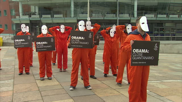 Exterior shots of Amnesty International Guantanamo Bay protesters gathered on streets of Belfast dressed in orange jump suits and masks on faces all...