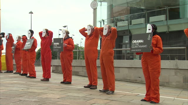 exterior shots of amnesty international protesters dressed in guantanamo bay outfits holding placards close guantanamo some with hands on heads like... - amnesty international stock videos & royalty-free footage