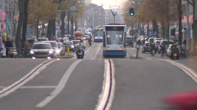 exterior shots of amsterdam city centre traffic with trams, cars and bicycles passing along a main road on 26 november 2019 in amsterdam, netherlands - amsterdam stock videos & royalty-free footage