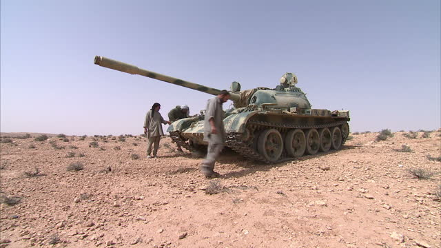 exterior shots of an abandoned gaddafi era libyan tank with a few rebel fighters stood around it abandoned libyan tank in desert on may 05 2011 in... - libyan civil war stock videos & royalty-free footage