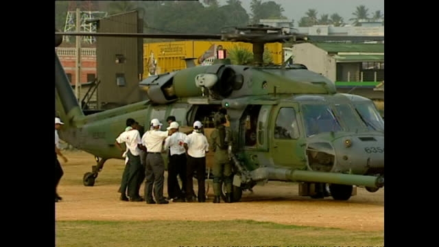 exterior shots of an american helicopter crew delivering boxes of aid and red cross workers unloading and preparing to distribute aid boxes as part... - wohltätigkeit stock-videos und b-roll-filmmaterial