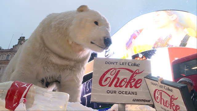 vídeos de stock, filmes e b-roll de exterior shots of an animatronic polar bear on an imitation ice flow studded with plastic bottles at the centre of a greenpeace demonstration in... - poluição do plástico