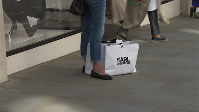 Exterior shots of an anonymous female shopper with a Karl Lagerfeld shopping bag stood next to the Chanel fashion shop on New Bond Street on August...
