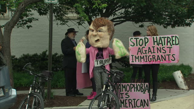 exterior shots of an anti donald trump protest outside the gop headquarters featuring a woman with a large paper mache trump effigy head waving fake... - künstlich stock-videos und b-roll-filmmaterial