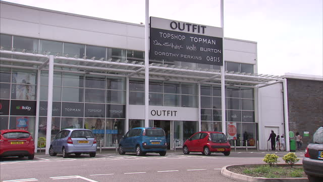 exterior shots of an arcadia group outlet unit 'outfit' with signs advertising topshop topman miss selfridge wallis burton dorothy perkins and... - kanton wallis stock-videos und b-roll-filmmaterial