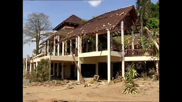 vídeos de stock, filmes e b-roll de exterior shots of an area devastated by the tsunami with damaged houses in a landscape strewn with mud and debris and recovery workers carrying away... - oceano índico