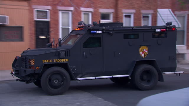 exterior shots of an armoured police state trooper vehicle driving through a deprived area of baltimore, the scene of rioting on april 28, 2015 in... - military land vehicle stock videos & royalty-free footage
