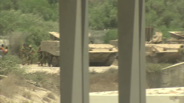 exterior shots of an army facility nearby a temporary medical hospital in ashkelon with soldiers walking around parked tanks outside - ashkelon stock videos and b-roll footage