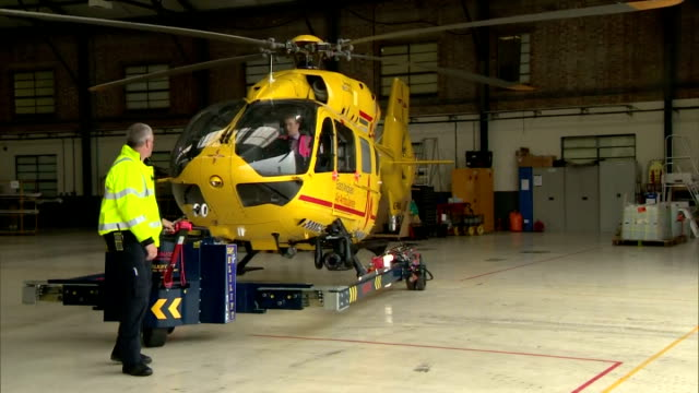 stockvideo's en b-roll-footage met exterior shots of an east anglian air ambulance being prepared and checked for flight inside a hanger at cambridge airport. on july 13, 2015 in... - pilot