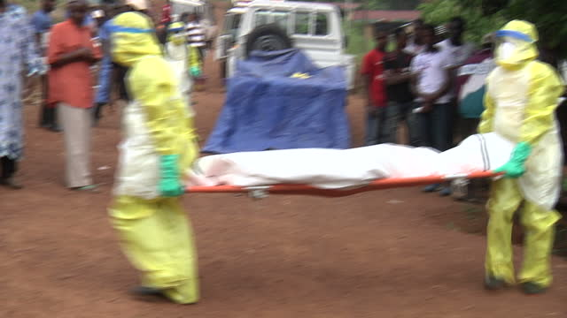 vídeos de stock, filmes e b-roll de exterior shots of an ebola burial team collecting a body from a house being watched by onlookers and prayers being read before the burial team take... - ébola