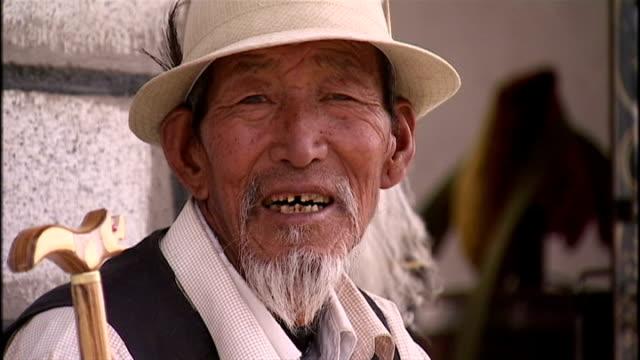 vídeos de stock, filmes e b-roll de exterior shots of an elderly tibetan man sat with a cane, and a tibetan shrine in lhasa, tibet on june 19, 2009 in unspecified, china. - autoimolação