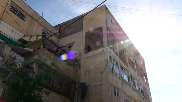 exterior shots of an electricity worker in silwan east jerusalem working on power lines outside the destroyed apartment of palestinian tram stop... - east jerusalem stock videos & royalty-free footage