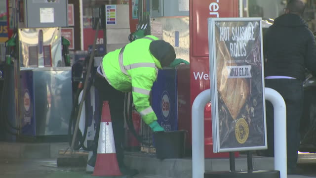 exterior shots of an esso petrol station in west london as a worker scrubs down and disinfects petrol pumps and nozzles during the coronavirus... - essential services stock videos & royalty-free footage