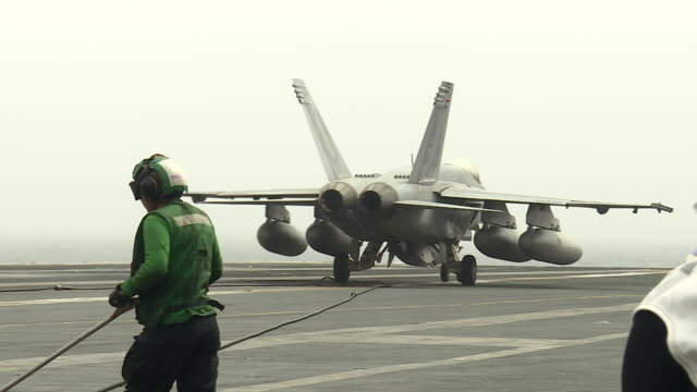 vídeos de stock e filmes b-roll de exterior shots of an f-18 hornet landing on the flight deck of the uss abraham lincoln aircraft carrier on 12 august 2019 in the arabian gulf, bahrain - avião de combate