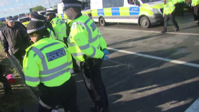 exterior shots of an injured protester being treated by paramedics during a protest by insulate britain protesters near heathrow airport with police... - insulator stock videos & royalty-free footage