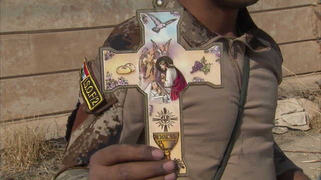 exterior shots of an iraqi soldier holding a catholic cross in front of a damaged but intact church in the town of bartella captured from isis... - religious equipment stock videos & royalty-free footage
