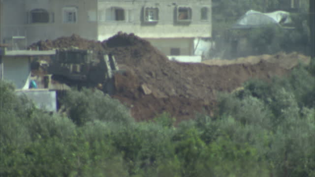 vídeos de stock e filmes b-roll de exterior shots of an israeli army tank next to the separation barrier and a watchtower at the erez crossing and an idf bulldozer clearing earth in... - israel