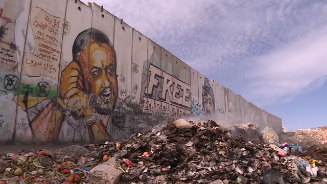 exterior shots of an israeli watchtower at a major west bank crossing point and graffiti on a section of separation barrier with a pile of... - blocco stradale video stock e b–roll
