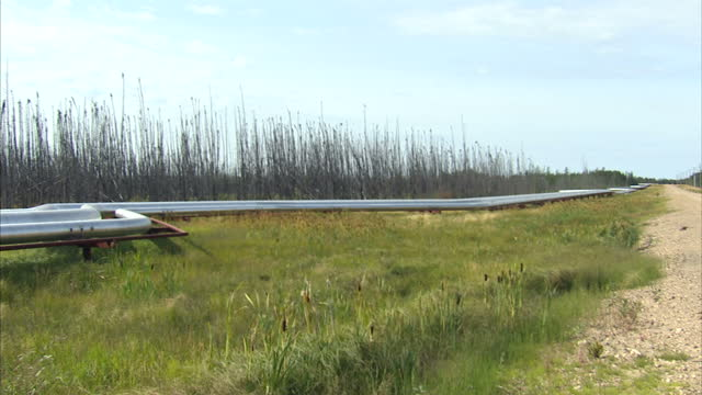 exterior shots of an oil pipeline alongside a road at the keystone xl facility on october 22, 2014 in alberta, canada. - pipeline stock-videos und b-roll-filmmaterial