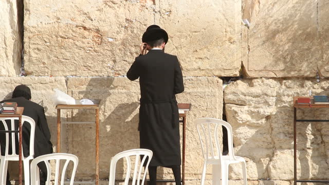 stockvideo's en b-roll-footage met exterior shots of an orthodox jewish man praying next to the western wall in jerusalem man praying at western wall on november 13 2013 in jerusalem... - orthodox jodendom