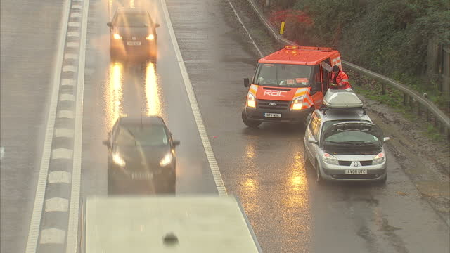 vídeos de stock e filmes b-roll de exterior shots of an rac technician attending to a vehicle broken down on the hard shoulder of the m4 motorway in wet weather near west drayton heavy... - vehicle breakdown