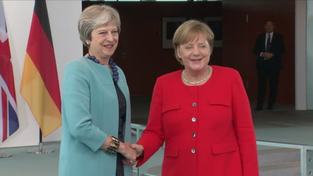 exterior shots of angela merkel and theresa may shaking hands at a podium before walking into the reichstag on 5 july 2018 in berlin germany - アンゲラ・メルケル点の映像素材/bロール