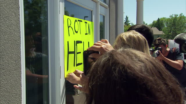 Exterior shots of animal rights activists posting a 'Rot in Hell' banner over the door to Walter Palmer's dental surgery on July 30 2015 in...