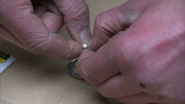 stockvideo's en b-roll-footage met exterior shots of anon man getting heroin out of wraps and measuring dosage on spoon and mixing it with liquid on december 02 2014 in manchester... - middelenmisbruik