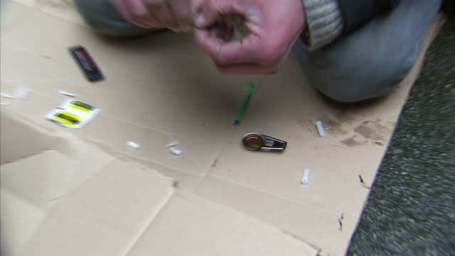 stockvideo's en b-roll-footage met exterior shots of anonymous man burning heroin mixture on spoon and adding more heroin powder to the mix on december 02 2014 in manchester united... - middelenmisbruik