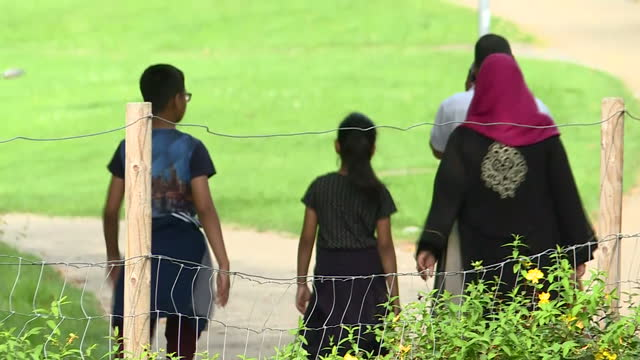 Exterior shots of anonymous Muslim family walking through park on 29th August 2017 London England
