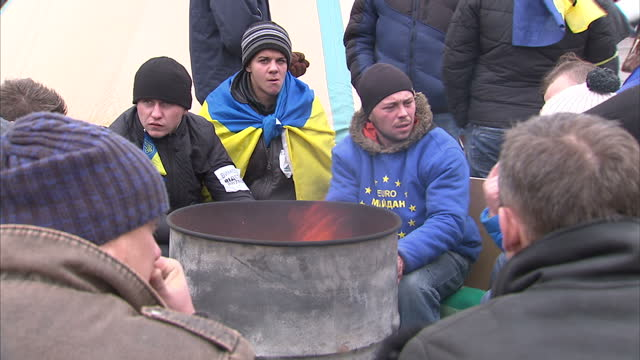 Exterior shots of anti government protesters gathered around a brazier for warmth wearing pro EU tops Protesters in Kiev continue to demonstrate on...