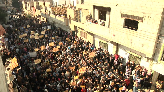 exterior shots of anti government protesters marching with banners in homs opposition supporters march in protests in homs on december 06 2011 in... - syrien stock-videos und b-roll-filmmaterial