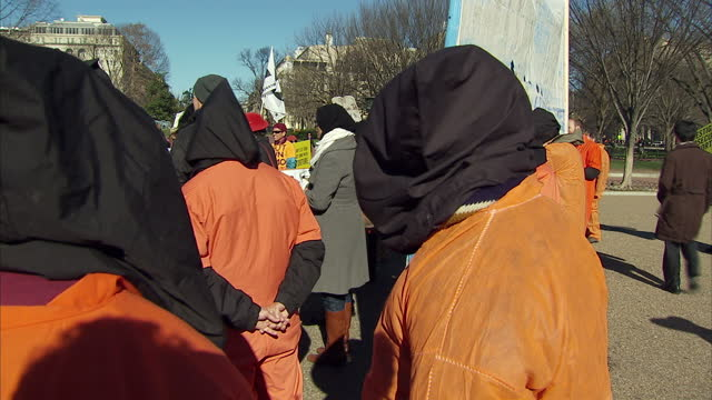 exterior shots of anti guantanamo bay protesters in orange jump suits and hoods holding up banners in a demonstration outside the white house on... - prisoner orange stock videos & royalty-free footage