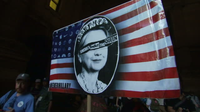 exterior shots of anti hillary clinton protesters outside the convention venue with a protest banner reading 'america indict the queen' on july 25,... - ペンシルベニア州点の映像素材/bロール
