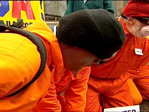 exterior shots of anti iraq war protesters dressed up as guantanamo bay detainees in orange all in ones boiler suits and have hands tied up and... - prisoner orange stock videos & royalty-free footage