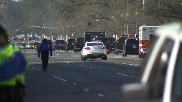 Exterior shots of anti NSA privacy campaigners protesting outside the Department of Justice building as a presidential motorcade surrounded by police...