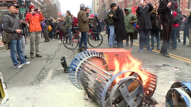 Exterior shots of anti social behaviour during an antiDonald Trump protest with waste bins being set alight and a protester dumping a car wheel into...