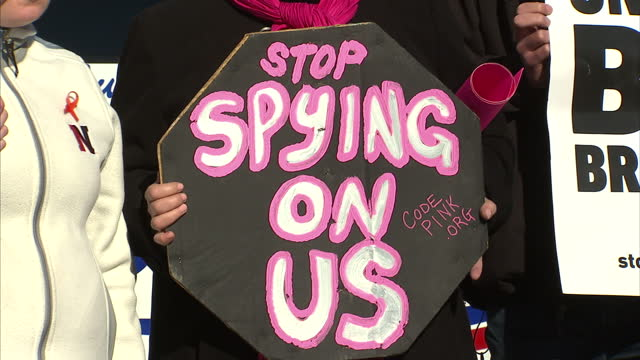 Exterior shots of anti spying protesters holding up signs 'Stop spying on us' 'Big Brother' etc outside the Department of Justice headquarters on...