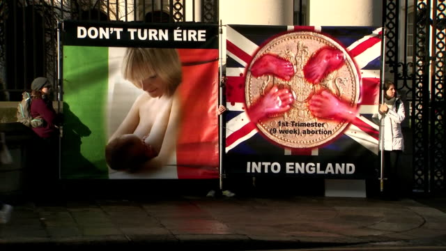 Exterior shots of antiabortion protesters holding banners outside the entrance to the Irish Parliament with graphic images of alleged aborted...
