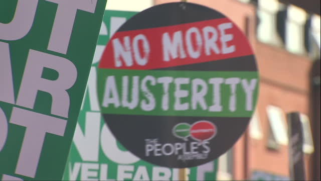 exterior shots of antiausterity protesters marching through manchester holding placards banners and balloons during demonstrations coinciding with... - marching stock videos and b-roll footage