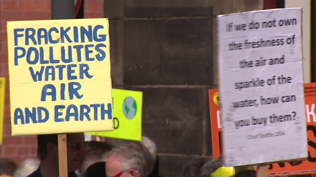 stockvideo's en b-roll-footage met exterior shots of antifracking protesters holding placards demonstrating against the approval of two shale gas exploration sites in lancashire>> on... - schalie