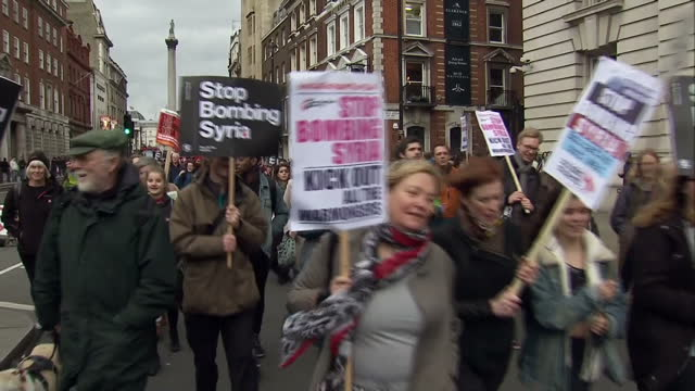 vídeos de stock, filmes e b-roll de exterior shots of antiwar protesters marching with banners placards reading stop bombing syria at a stop the war coalition peace march on december 11... - stop placa em inglês