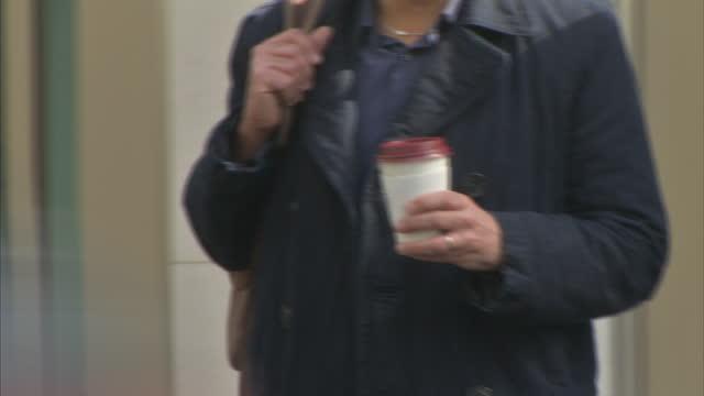 exterior shots of anynymous people carrying disposable coffee cups. - slit och släng bildbanksvideor och videomaterial från bakom kulisserna