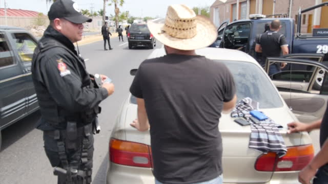 Exterior shots of armed and masked Mexican police officers stopping cars at a checkpoint and carrying out pat down searches on some drivers in...