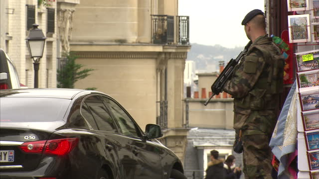 exterior shots of armed french soldiers on patrol on a touristy street in the montmartre district on november 17, 2015 in paris, france - weapon stock videos & royalty-free footage