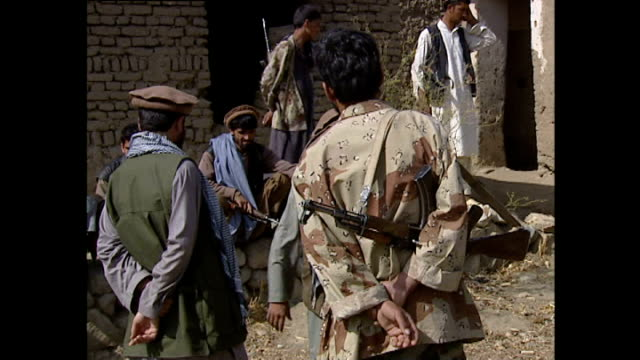 exterior shots of armed northern alliance soldiers milling and patrolling around a compound.>> on october 14, 2001 in parwan province, afghanistan. - 14 15 years stock videos & royalty-free footage